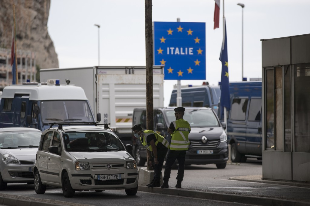 FILE - In this Monday, June 15, 2020 file photo, French gendarmes approach a car at the Saint-Ludovic border check point on the Franco-Italian border ...