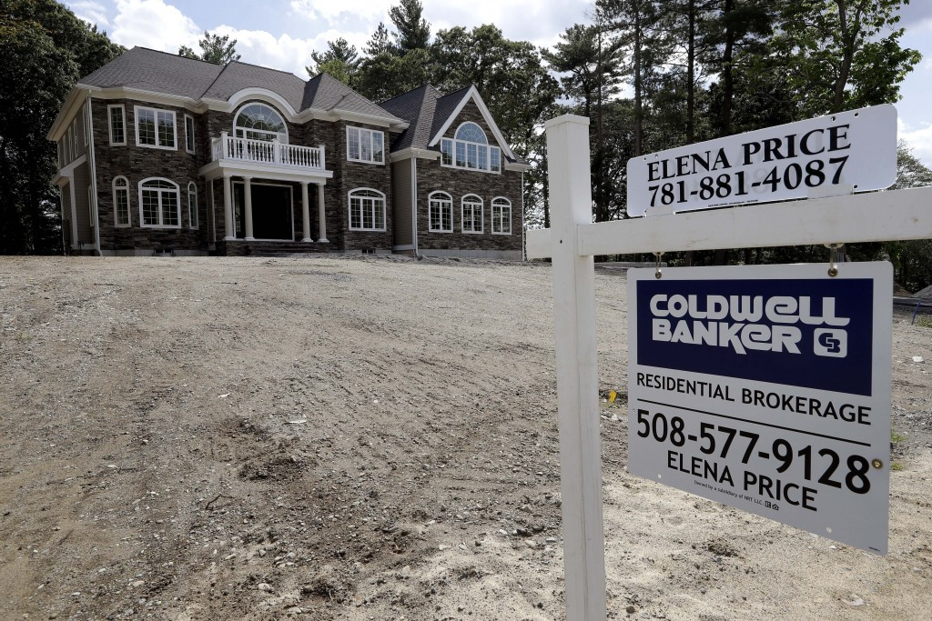 FILE - In this Sept. 3, 2019 file photo a sign rests in front of a newly constructed home, in Westwood, Mass. U.S. home prices rose in April for the e...