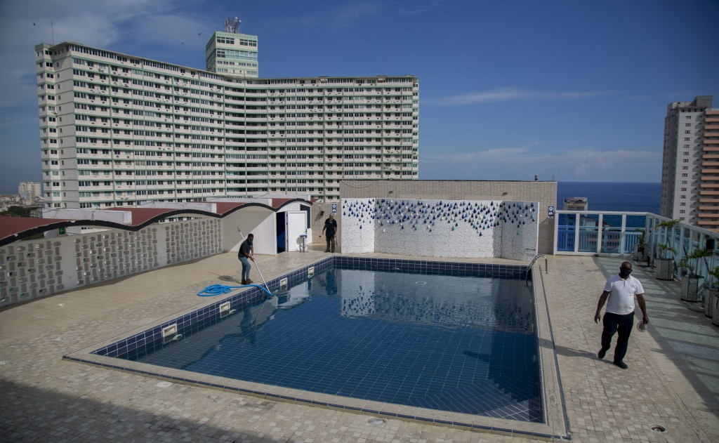 Workers do maintenance on the rooftop pool of the Capri Hotel during a lockdown affecting tourism to curb the spread of the COVID-19 pandemic in Havan...