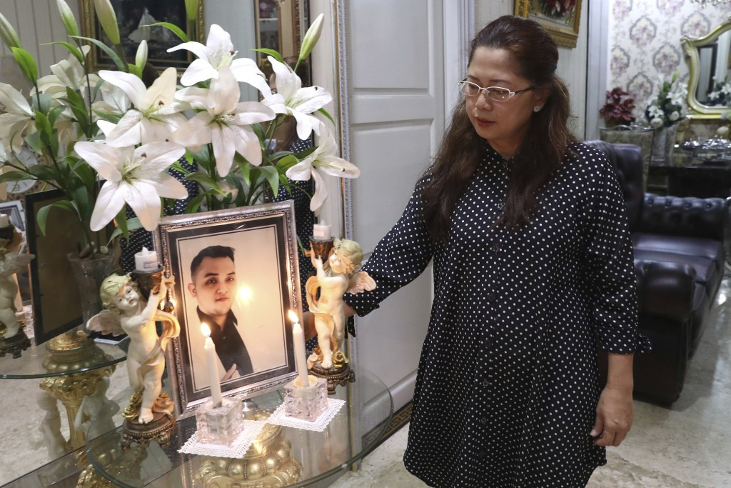 Herlina Simbala looks at a portrait of her son, Dr. Michael Robert Marampe during an online memorial service to mark the 40th day since Marampe passed...