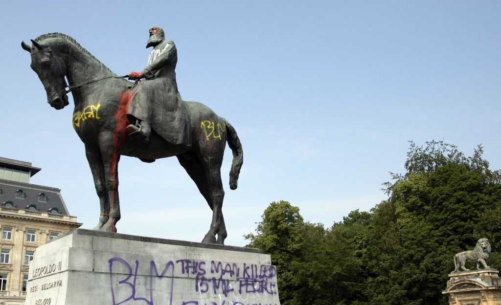 FILE - In this Wednesday, June 10, 2020 file photo, a statue of Belgium's King Leopold II is smeared with red paint and graffiti in Brussels. With the...