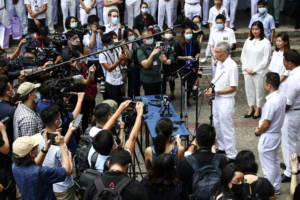 People's Action Party Secretary-General and Singaporean Prime Minister Lee Hsien Loong, right, fields questions from the media at a nomination center ...