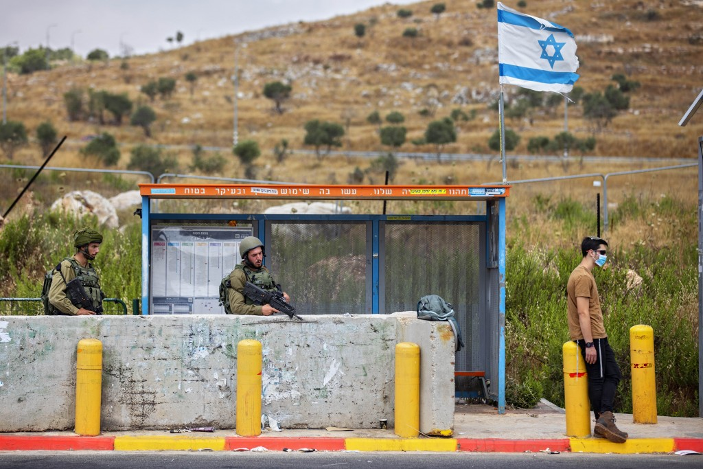 Israeli soldiers guard a bus station at the Tapuach junction next to the West Bank city of Nablus, Tuesday, June 30, 2020. Israeli Prime Minister Benj...