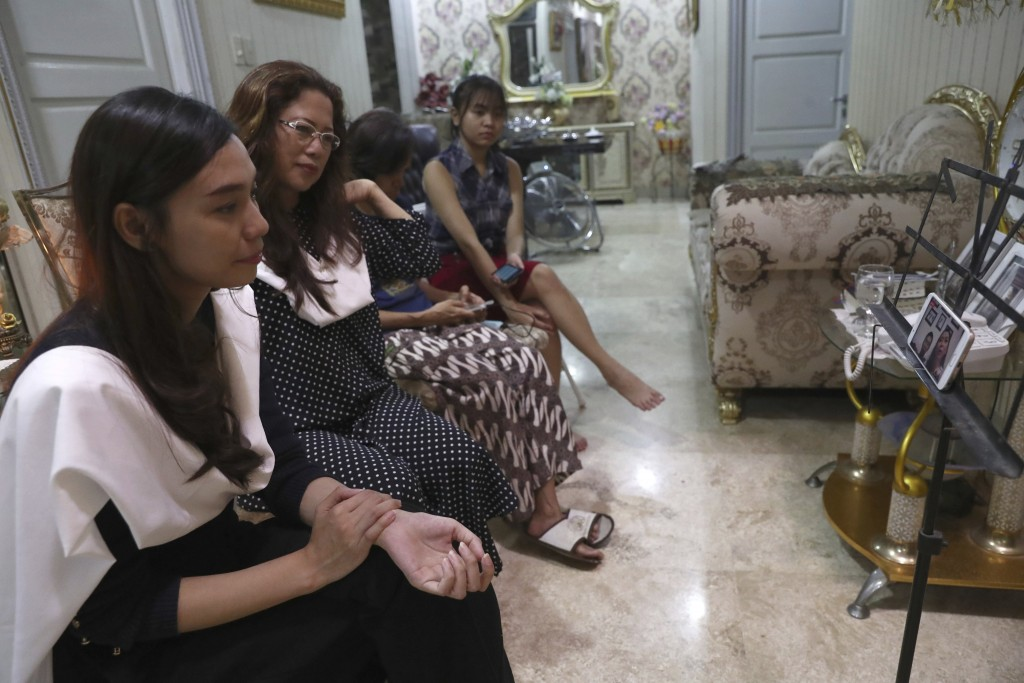 Fiance Tri Novia Septiani, left, and mother Herlina Simbala, second from left, of Dr. Michael Robert Marampe attend an online memorial service to mark...