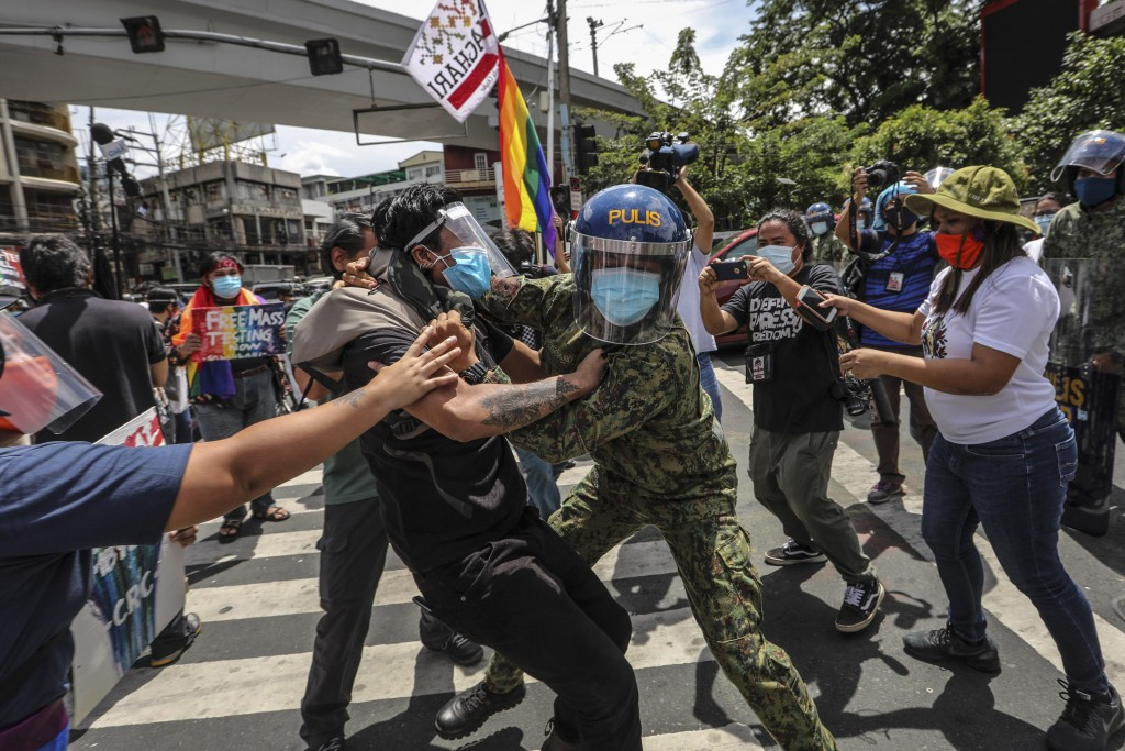 Police wearing face masks arrest protesters during a LGBTQ pride march in Manila, Philippines, Friday June 26, 2020. Philippine police  arrested 20 pr...