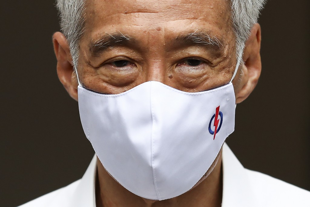People's Action Party Secretary-General and Singaporean Prime Minister Lee Hsien Loong wears a mask adorned with his party logo as he waits to field q...
