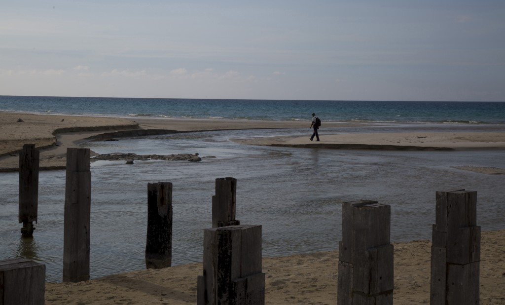 A man walks on Boca Ciega beach where swimming is restricted due to the COVID-19 pandemic in Havana, Cuba, Monday, June 22, 2020. With coronavirus cas...