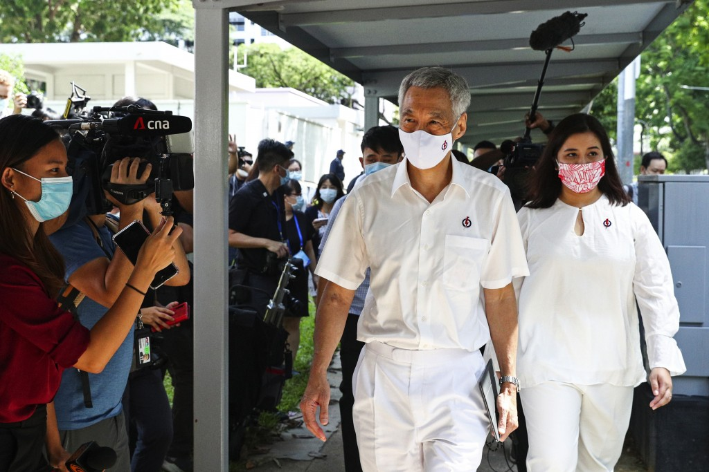 People's Action Party Secretary-General and Singaporean Prime Minister Lee Hsien Loong, center, arrives at a nomination center with his team to submit...
