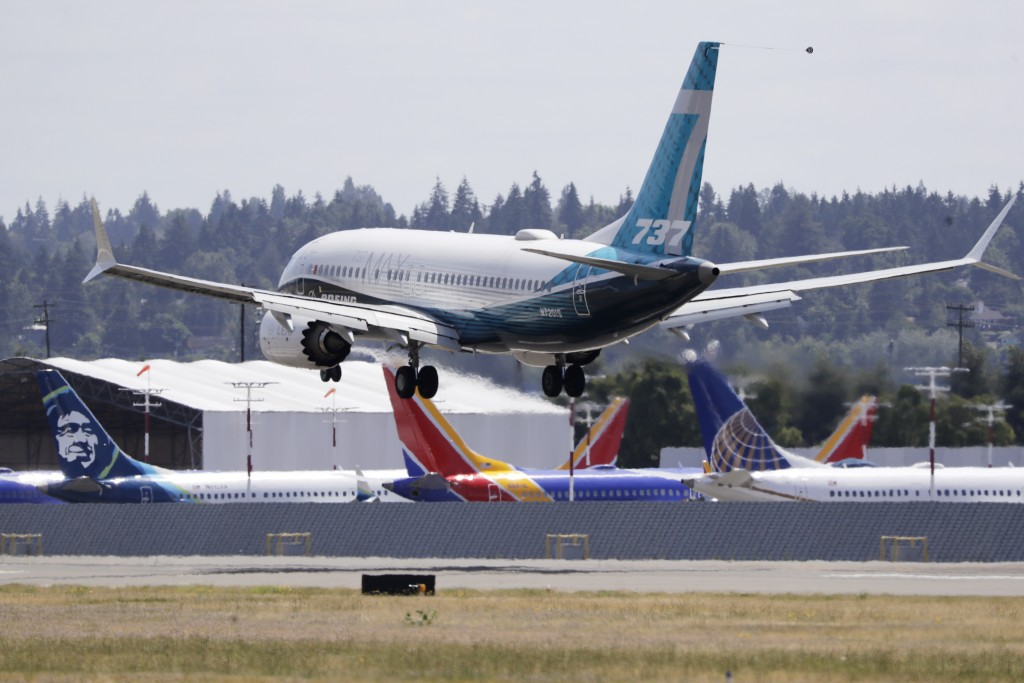 A Boeing 737 MAX jet heads to a landing and past grounded 737 MAX jets behind at Boeing Field following a test flight Monday, June 29, 2020, in Seattl...