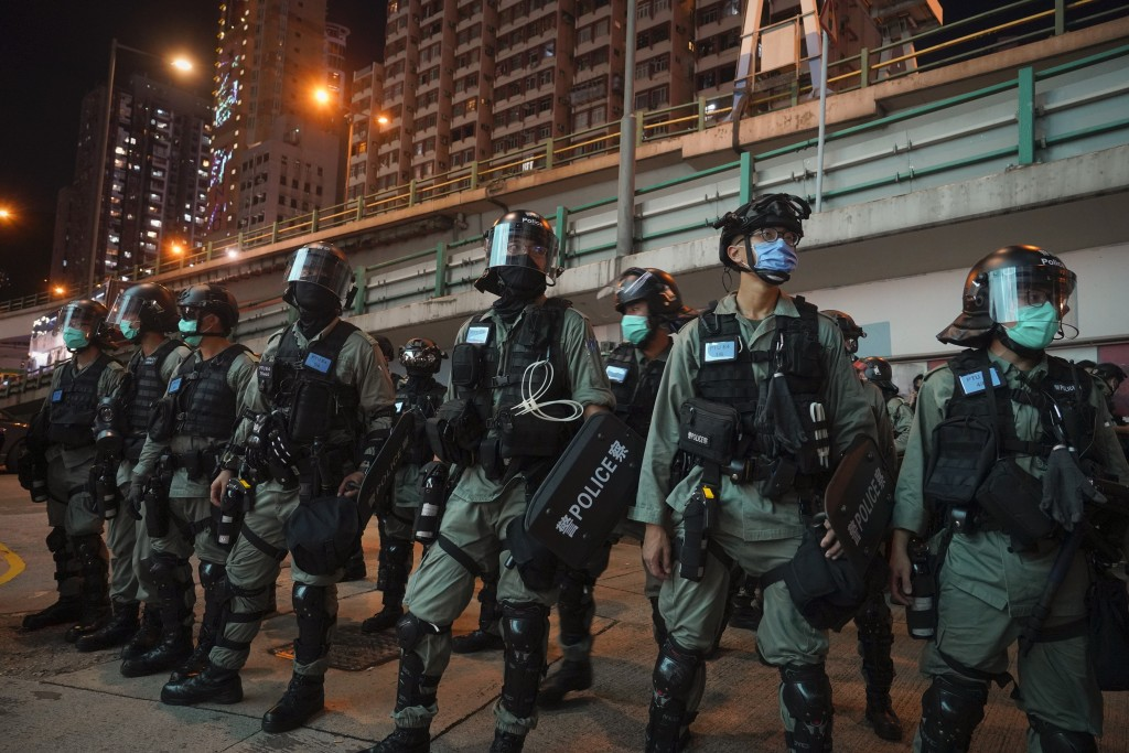 Riot police stand guard after pushing back protesters demonstrating against the new security law during the anniversary of the Hong Kong handover from...