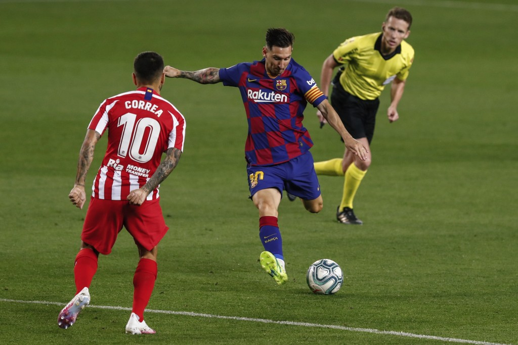 Barcelona's Lionel Messi, center, kicks the ball in front Atletico Madrid's Angel Correa during the Spanish La Liga soccer match between FC Barcelona ...