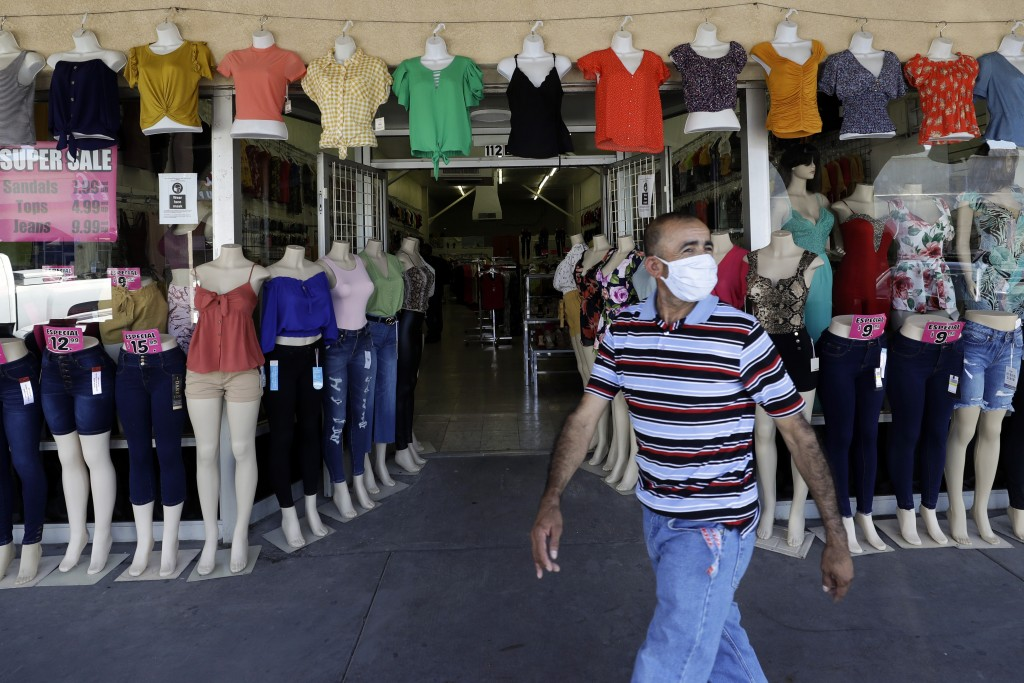A man passes a clothing shop Tuesday, June 30, 2020, in Calexico, Calif. Saddled with a surge in positive cases and hospitalizations for the new coron...
