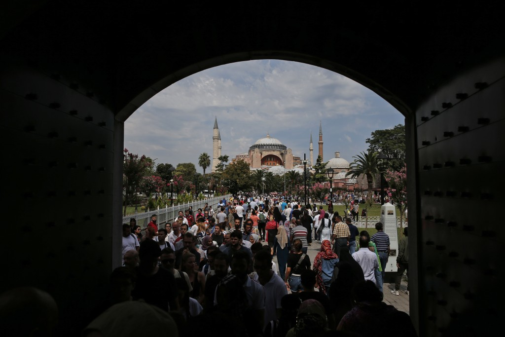 FILE - In this Friday, Aug. 17, 2018 file photo, visitors walk towards the Byzantine-era Hagia Sophia, one of Istanbul's main tourist attractions, in ...