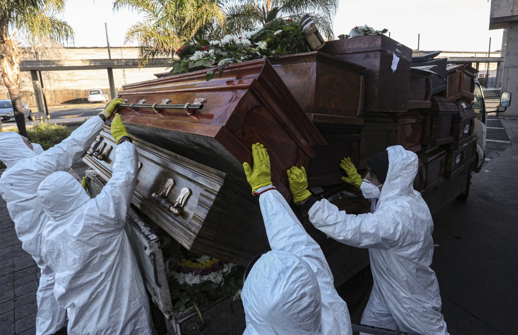 Workers collect and stack the coffins of people that have been recently cremated amid the new coronavirus pandemic at La Recoleta cemetery, amid the n...