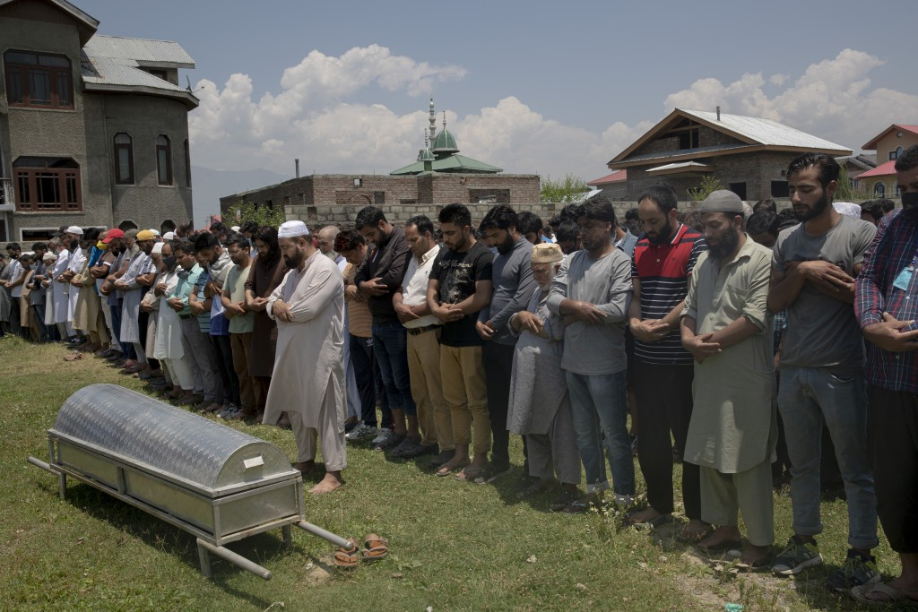 Relatives and neighbors offer prayers near the coffin of civilian Bashir Ahmed Khan, during his funeral on the outskirts of Srinagar, Indian controlle...