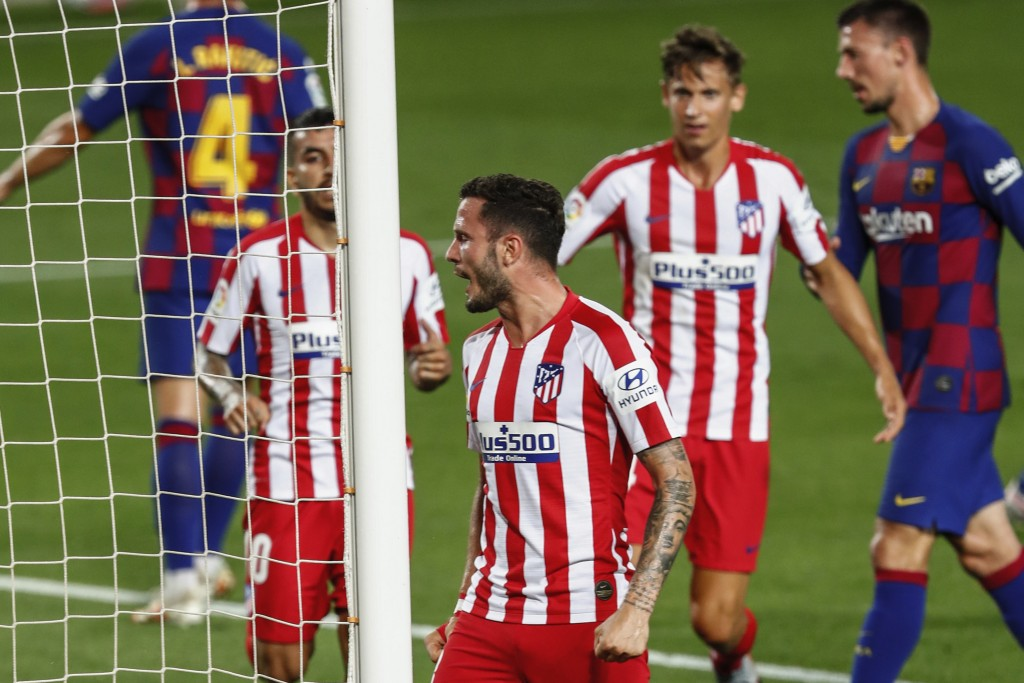 Atletico Madrid's Saul, center, celebrates after scoring his side's second goal during the Spanish La Liga soccer match between FC Barcelona and Atlet...
