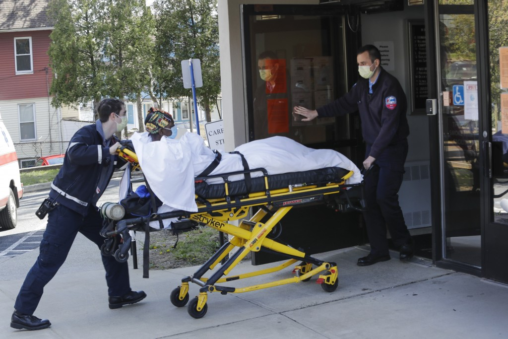 FILE - In this April 22, 2020, file photo medical workers bring a patient to the Northbridge Health Care Center in Bridgeport, Conn. A report from Sen...