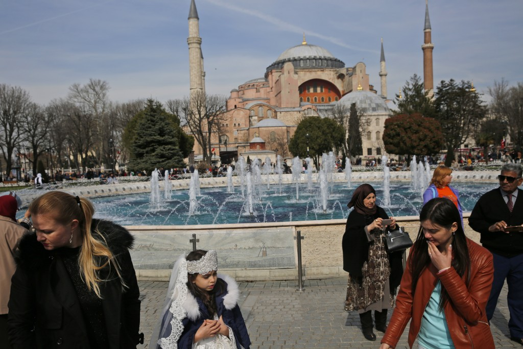 FILE - In this Friday, March 24, 2017 file photo, people walk backdropped by the Byzantine-era Hagia Sophia, one of Istanbul's main tourist attraction...