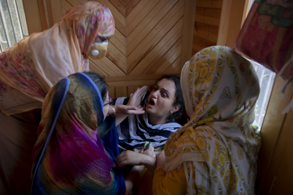 Relatives comfort the grieving daughter of civilian Bashir Ahmed Khan at their residence on the outskirts of Srinagar, Indian controlled Kashmir, Wedn...