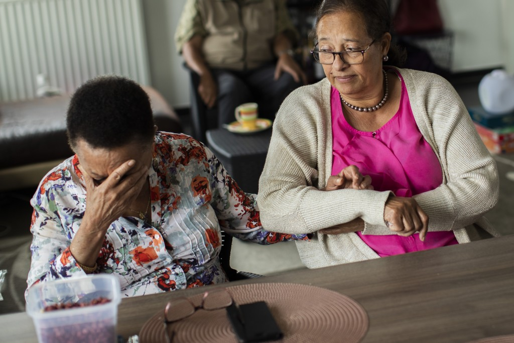 In this photo taken on Monday, June 29, 2020, Marie-Jose Loshi, left, cries as she is comforted by her friend Monique Bitu Bingi during an interview w...