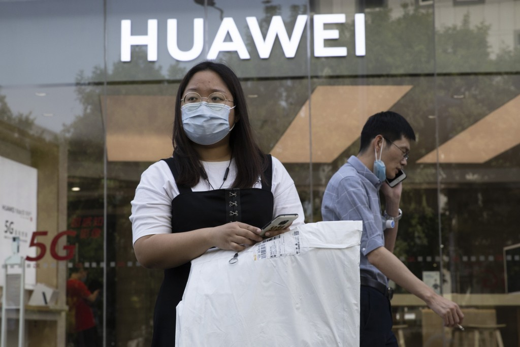 Residents wearing masks to curb the spread of the coronavirus past by a Huawei shop in Beijing on Friday, June 5, 2020. China on Wednesday demanded Wa...
