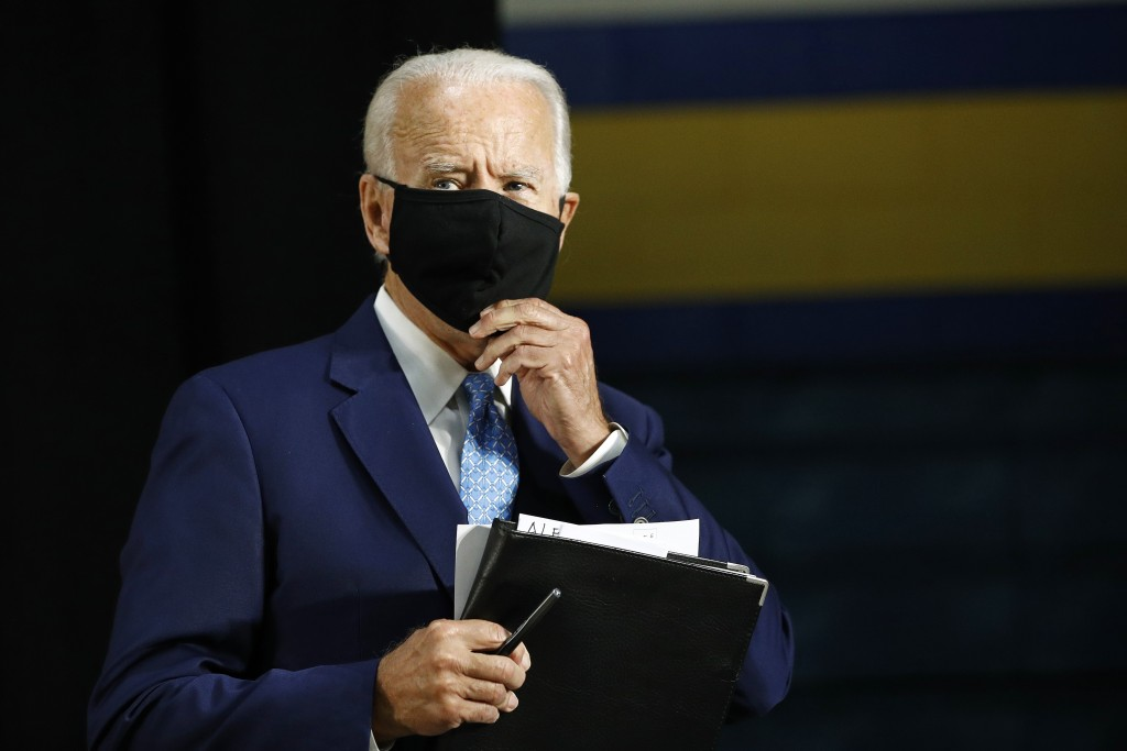 Democratic presidential candidate, former Vice President Joe Biden puts on a face mask to protect against the spread of the new coronavirus as he depa...
