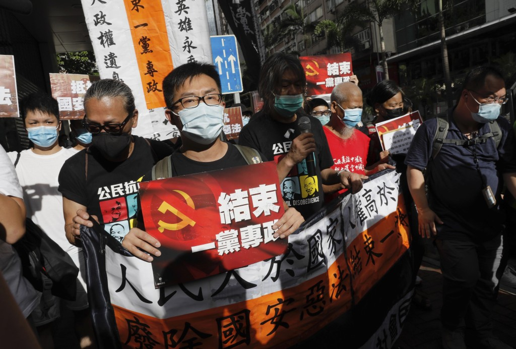 "Pro-democracy protesters shout slogans "" Stop One Party Rolling"" as they march toward the flag raising ceremony marking the anniversary of the Hong Ko..."