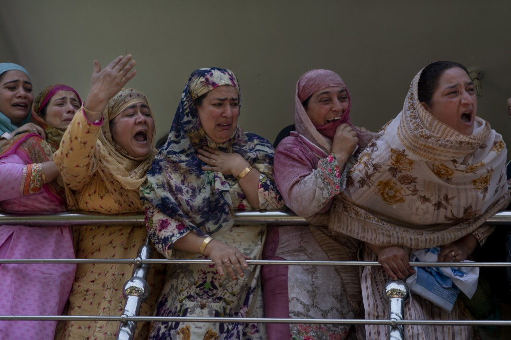 Relatives of Kashmiri civilian Bashir Ahmed Khan grieve as they watch his funeral on the outskirts of Srinagar, Indian controlled Kashmir, Wednesday, ...