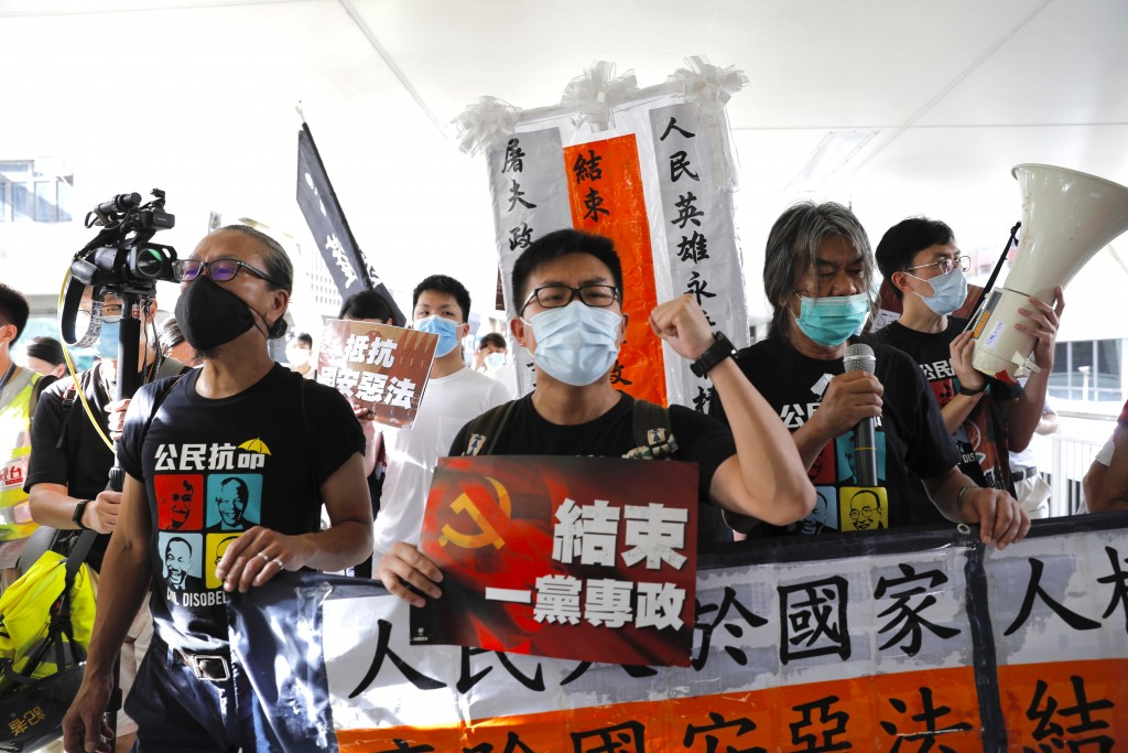 "Pro-democracy protesters shout slogans "" Stop One Party Rolling"" as they march toward the flag raising ceremony, in Hong Kong, Wednesday, July 1, 2020..."