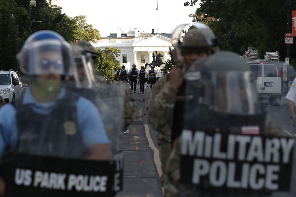 FILE - In this Monday, June 1, 2020, file photo police clear the area around Lafayette Park and the White House in Washington, as demonstrators gather...