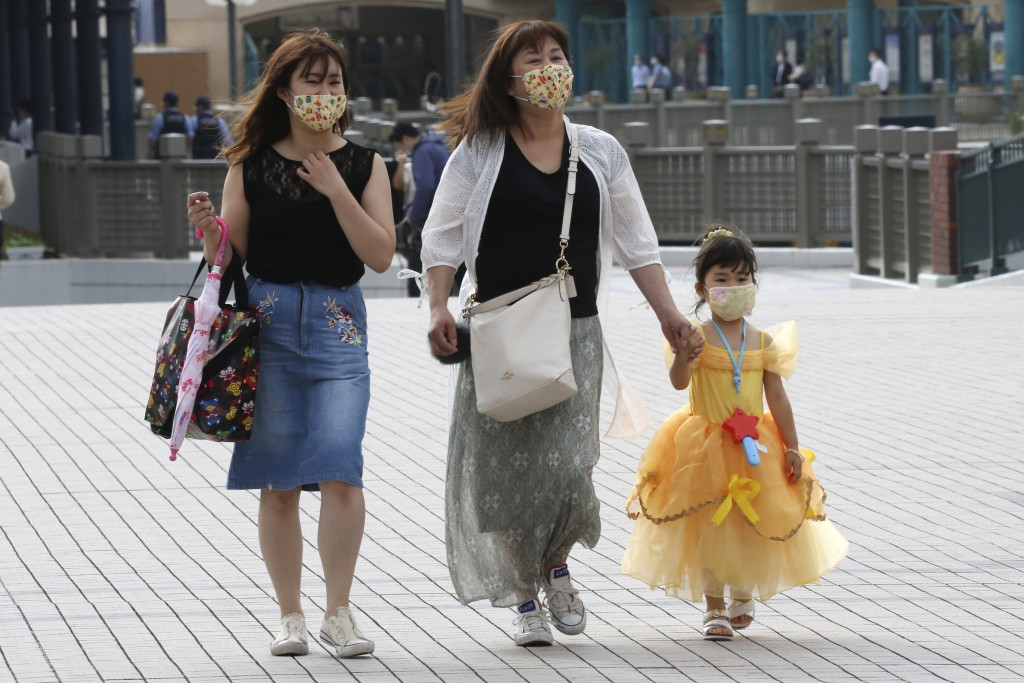 People wearing face masks to protect against the spread of the new coronavirus walk toward the entrance to Tokyo Disneyland in Urayasu, near Tokyo, We...