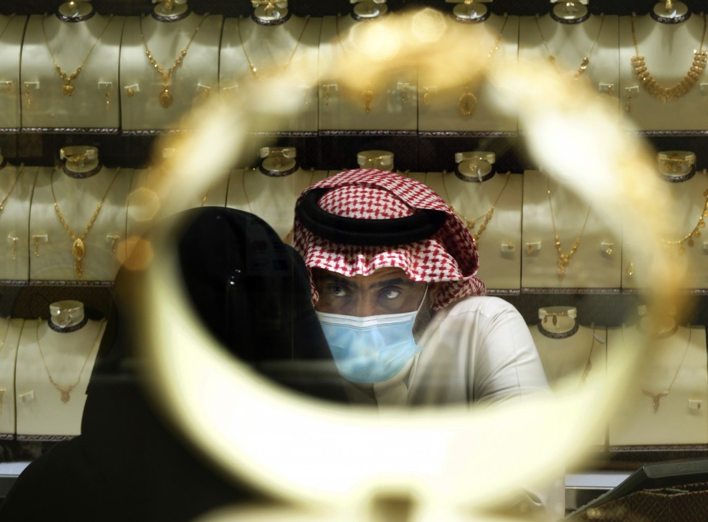 A Saudi vendor is seen through a bracelet as a woman buys jewels at the gold market a day before the expected increase of VAT from 5% to 15%, in Jidda...