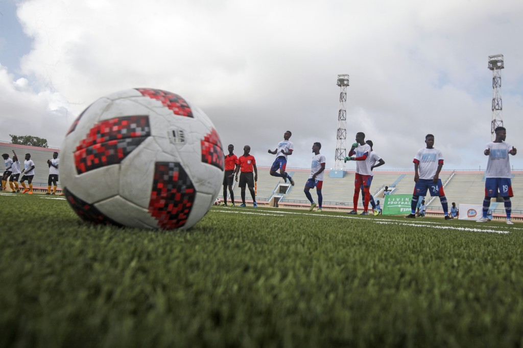 Football players warm up during the reopening of the stadium in Mogadishu, Somalia Tuesday, June 30, 2020. At least three mortar blasts struck the Mog...