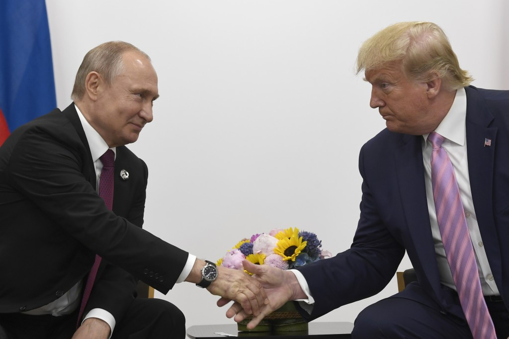 FILE - In this June 28, 2019, file photo President Donald Trump, right, shakes hands with Russian President Vladimir Putin, left, during a bilateral m...