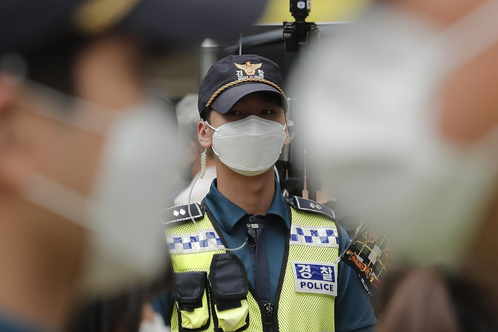 Police officers wearing face masks to help protect against the spread of the new coronavirus stand guard near the Japanese embassy in Seoul, South Kor...