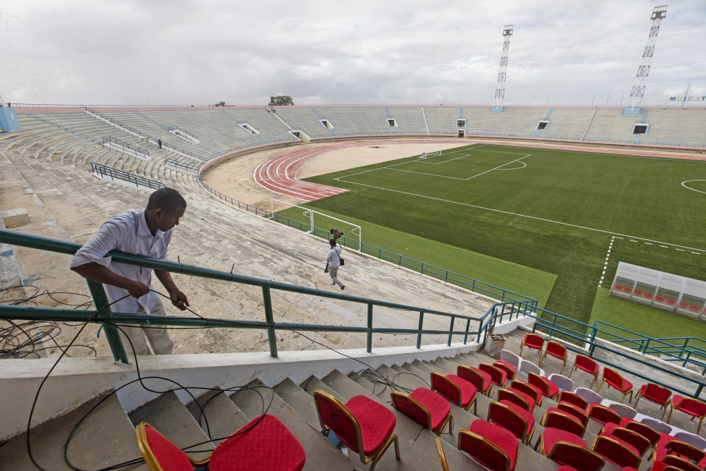 A man runs cables prior to the reopening of the soccer stadium in Mogadishu, Somalia Tuesday, June 30, 2020. At least three mortar blasts struck the M...