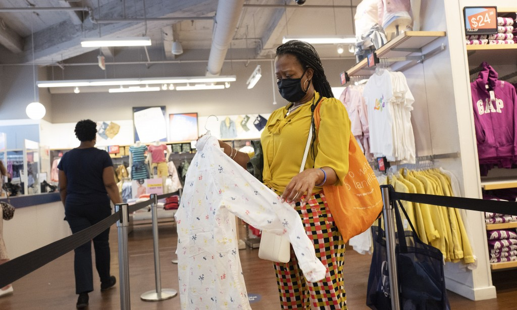 A woman shops for clothing in a Gap store during the coronavirus pandemic, Tuesday, June 30, 2020, in New York. New York City may begin Phase 3 reopen...