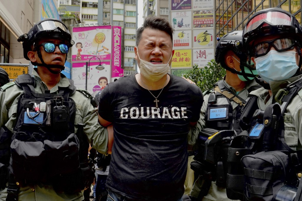 Police detain a protester after spraying pepper spray during a protest in Causeway Bay before the annual handover march in Hong Kong, Wednesday, July....