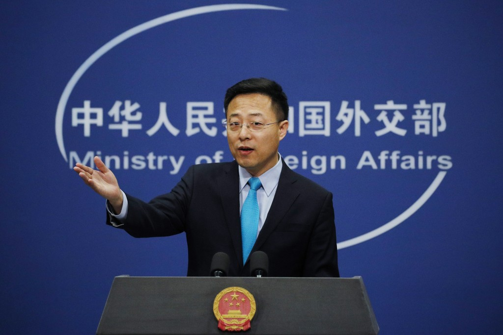 FILE - In this Feb. 24, 2020, file photo, Chinese Foreign Ministry spokesman Zhao Lijian gestures as he speaks during a daily briefing at his ministry...
