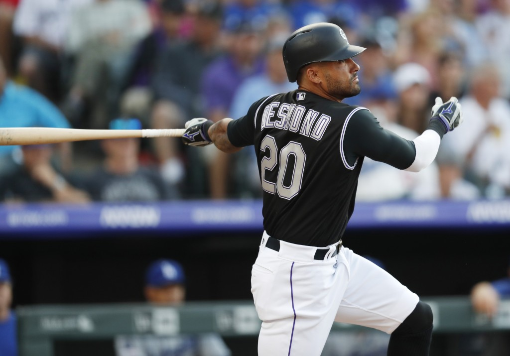 FILE - In this July 29, 2019, file photo, Colorado Rockies' Ian Desmond follows the flight of his triple off Los Angeles Dodgers starting pitcher Kent...
