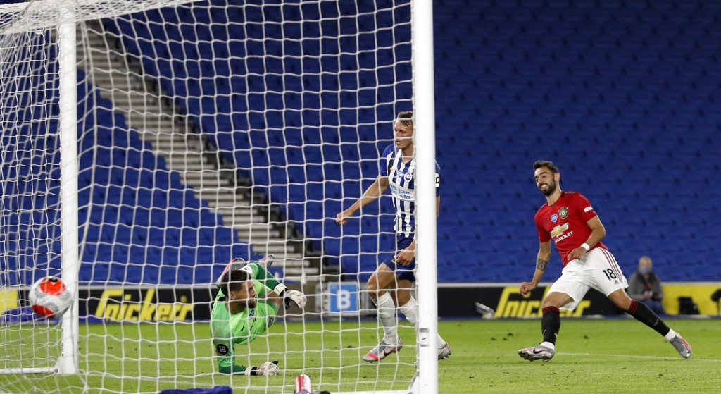 Manchester United's Bruno Fernandes, right, scores his side's third goal during the English Premier League soccer match between Brighton & Hove Albion...
