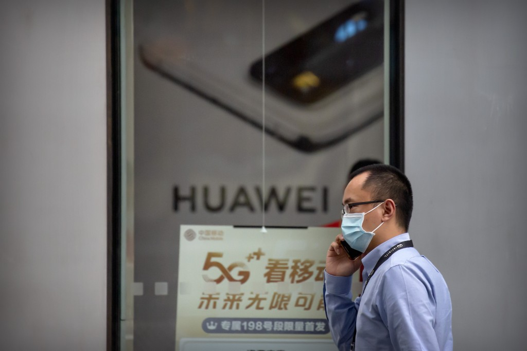 A man wearing a face mask to protect against the new coronavirus talks on his smartphone as he walks past a Huawei store in Beijing, Wednesday, July 1...