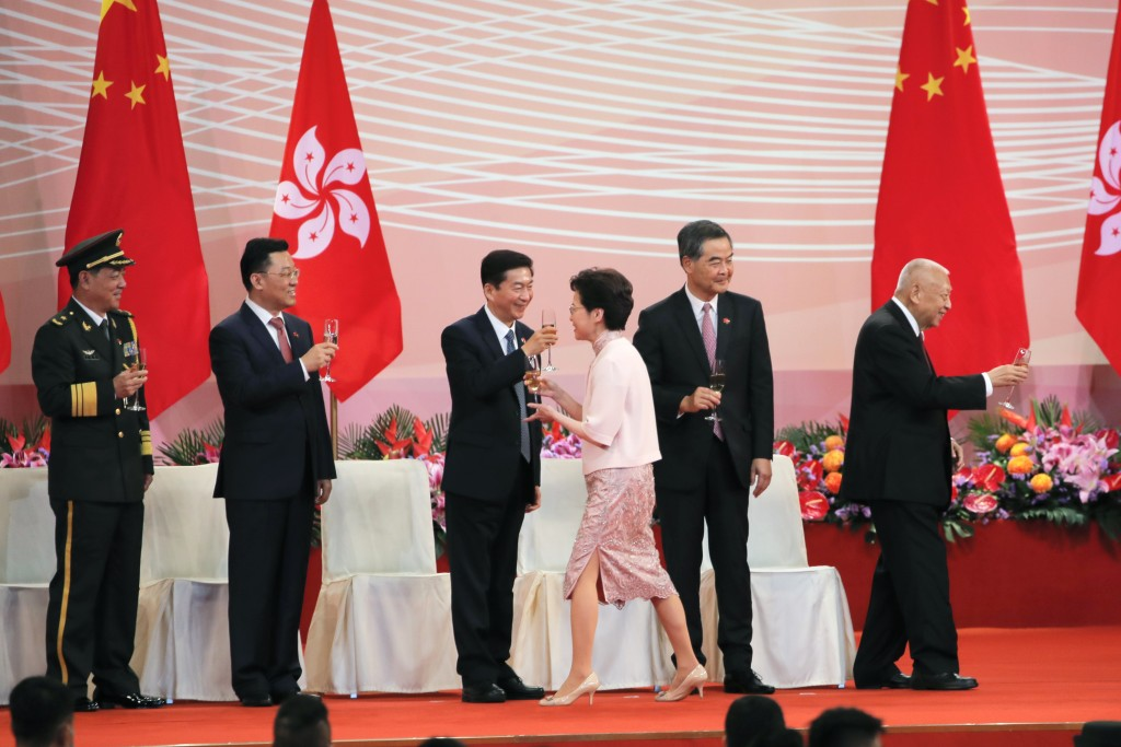 Hong Kong's Chief Executive Carrie Lam, center right, toasts with Luo Huining, center left, head of China's liaison office in Hong Kong, and others gu...