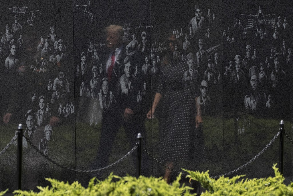 FILE - In this June 25, 2020, file photo reflected in a memorial, President Donald Trump, accompanied by first lady Melania Trump, arrives at the Kore...