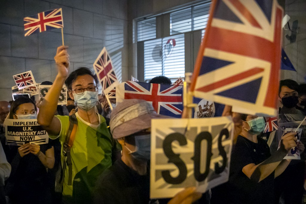 FILE - In this Oct. 23, 2019, file photo, demonstrators wave British flags during a rally outside the British Consulate in Hong Kong. From Tokyo to Br...