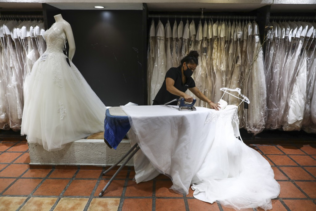 A woman wearing a mask to curb the spread of the new coronavirus irons a wedding dress at a store in Mexico City, Tuesday, June 30, 2020. (AP Photo/Ed...