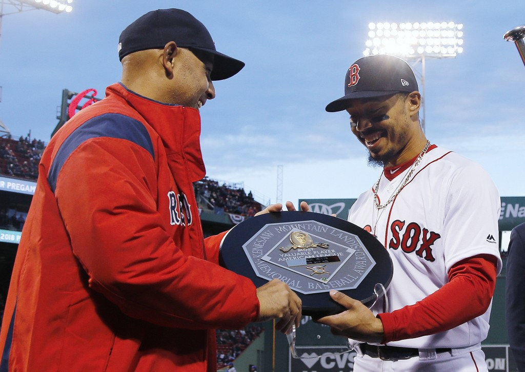 FILE - In this April 11, 2019, file photo, Boston Red Sox manager Alex Cora, left, presents right fielder Mookie Betts with the 2018 AL MVP Award befo...
