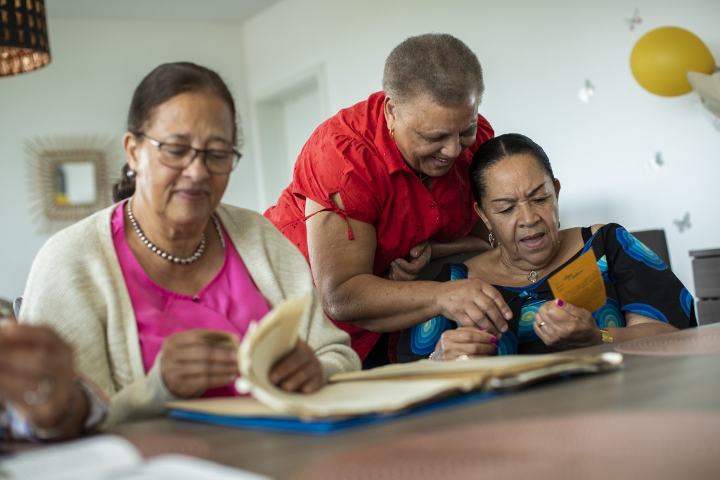 In this photo taken on Monday, June 29, 2020, Lea Tavares Mujinga, right, speaks with her friend Simone Ngalula, center, as they look over papers with...