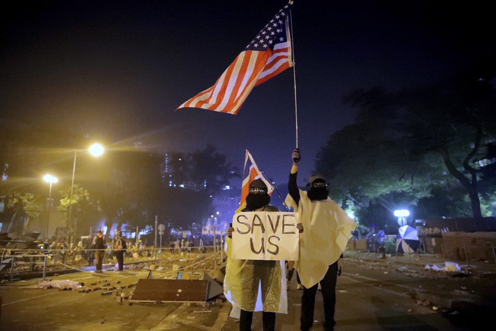 "FILE - In this Nov. 18, 2019, file photo, protesters hold British and American flags and a sign reading ""Save us"" as they stand near Hong Kong Polytec..."