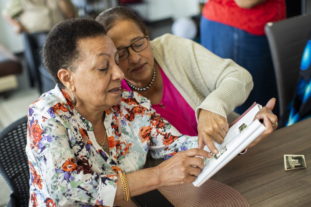 In this photo taken on Monday, June 29, 2020, Marie-Jose Loshi, left, speaks with her friend Monique Bitu Bingi as they look over old photos during an...